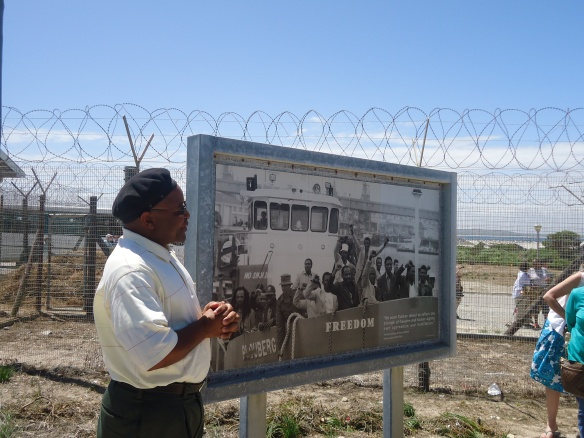 island ex-prisoner and tour guide Ntando standing next to a picture of the last island prisoners to leave the island  in May 1991.