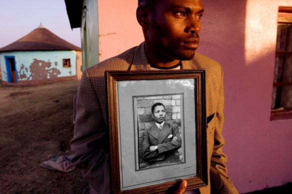'Madiba' Nelson Rolihlahla Mandela was raised in the rural Transkei, born into the Xhosa Thembu Royal family. At age 22, after studying at the prestigious Fort Hare University when the portrait in this photograph was made, 'Madiba' returned to the village to find that his Chieftan father had arranged marriages for him and his adopted brother, Justin. It was at this moment that Mandela, resisting, took a train to Johannesburg and was quickly catapulted into a leadership role to end apartheid. The young man in this photograph, holding the portrait of 'Madiba' in college, is a distant relative who lives in the village of Mqhekezweni, in the Transkei, where this original portrait still sits on the mantel of the family home. Read more: A Tribute to Nelson Mandela by Pulitzer Winner David