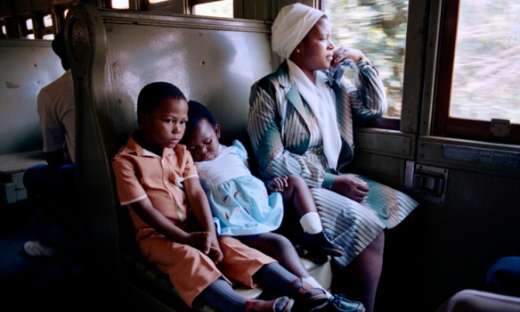 A South African mother travels with her children in a segregated train car. 1986.