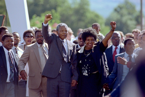 """The world looked on as international hero Mandela walked out of prison after 27 years on Feb. 11, 1990, with his wife, Winnie. At 6'3"""" tall, """"Madiba"""" and his presence met the stature that the world had expected."""